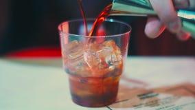 Hällande alkoholdryck för bartender in i exponeringsglas med iskuber Bartender som gör whisky arkivfilmer