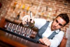 Hällande alkoholdryck för bartender in i små exponeringsglas på stång royaltyfria bilder