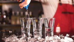 Hällande alkoholdryck för yrkesmässig manlig bartender i sköt exponeringsglas i en nattklubb lager videofilmer