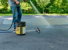 Hällande asfalttätningsmedel på körbanan Arkivfoto
