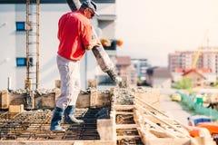 Hällande betong för byggnadsarbetare i konstruktionsplatsen, byggande detaljer, bransch fotografering för bildbyråer