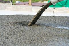 Hällande betong från en konkret blandare Arbetet av hällande betong för folk arkivfoton