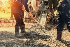 hällande betong med arbetarblandningcement på konstruktion Royaltyfri Bild