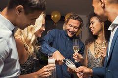 Hällande champagne för man i flöjter fotografering för bildbyråer