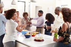Hällande champagne för mellersta åldrig afrikansk amerikanman som hemma firar med hans familj för tre utveckling royaltyfri fotografi