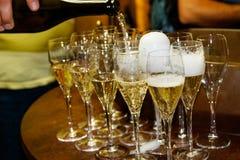Hällande champagne för uppassare från en flaska in i exponeringsglaset arkivfoton