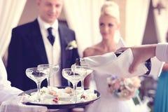 Hällande champagne för uppassare i exponeringsglasen Royaltyfria Foton