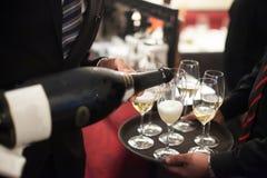 Hällande champagne för uppassare in i vinexponeringsglaset i restaurang blurriness arkivbilder