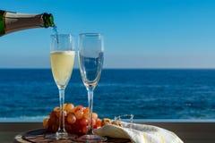 Hällande Champagne för uppassare, prosecco eller cava itu exponeringsglas på utvändig terrass med havssikt fotografering för bildbyråer