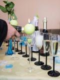 Hällande champagne in i ett exponeringsglas Arkivbild