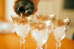 Hällande champagne in i exponeringsglas som står på tabellen Royaltyfri Bild