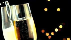 Hällande champagne in i flöjter med guld- bubblor med guld- abstrakt begrepp som blinkar den suddiga julgranen, tänder bokeh