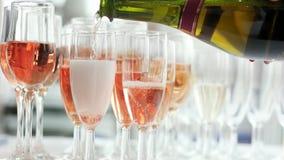 Hällande champagneexponeringsglas efter exponeringsglas som mousserar rosdrinken, kvinnainnehavflaska och häller vin arkivfilmer