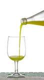 Hällande citronjuice från flaskan in i exponeringsglas Fotografering för Bildbyråer