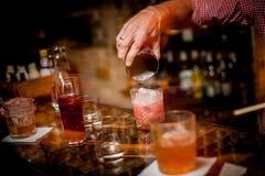 Hällande coctail för bartender in i ett exponeringsglas royaltyfri fotografi