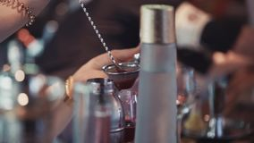 Hällande coctail för bartender i exponeringsglas på stångställningen drinkar _ beverly arkivfilmer