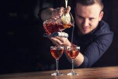 Hällande coctailalkoholdryck Manhattan för bartender royaltyfri fotografi
