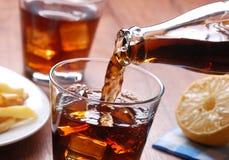 Hällande cola i exponeringsglas fotografering för bildbyråer
