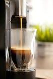Hällande espressokaffe in i en kopp Royaltyfri Fotografi
