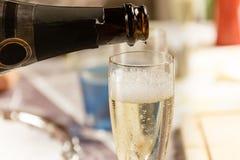 Hällande exponeringsglas av champagne Royaltyfri Foto
