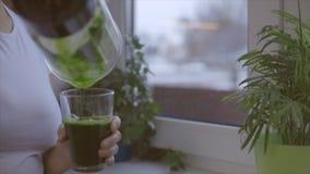 Hällande exponeringsglas för kvinna av den gröna nya smoothien i köket lager videofilmer