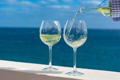 Hällande exponeringsglas för uppassare av vitt vin på utomhus- terrass med hav V royaltyfria bilder