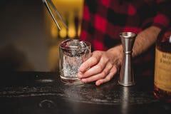 Hällande is för bartender i exponeringsglas Bartender som förbereder coctaildrinken Royaltyfria Foton