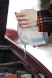 Hällande frostskyddsvätskapackningsvätska in i vindrutapackning tankar arkivbilder