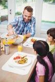 Hällande fruktsaft för fader i exponeringsglas med barn Royaltyfria Bilder