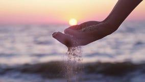 Hällande havssand för kvinnlig hand till och med henne fingrar på solnedgången mot en havbakgrund med linssignalljuseffekt långsa lager videofilmer