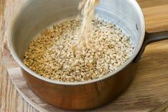Hällande hela kornråriers in i den Wood tabellen för kopparkrukan vinkar lantligt kök som inre sunt bantar den medelhavs- fiberkä Arkivbilder