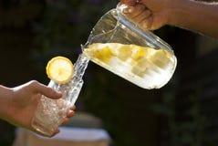 Hällande hemlagad lemonade in i exponeringsglas Arkivbild