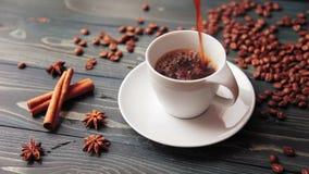 Hällande hemlagat kaffe in i en kopp Kaffebönor, kanelbruna pinnar och en smula på en trätabell arkivfilmer