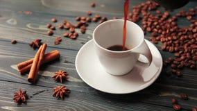 Hällande hemlagat kaffe in i en kopp Kaffebönor, kanelbruna pinnar och en smula på en trätabell lager videofilmer