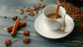 Hällande hemlagat kaffe in i en kopp Kaffebönor, kanelbruna pinnar och en smula på en trätabell stock video