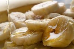 Hällande honung över bananstycken arkivbilder