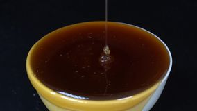 Hällande honung i den vita bunken Closeuphonungstekflott i svart bakgrund, makro stock video