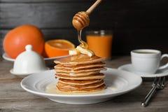 Hällande honung på läckra pannkakor med smör fotografering för bildbyråer
