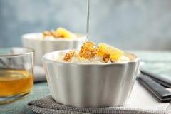 Hällande honung på risgrynsgröt med valnötter och orange skiva i ramekin arkivbild