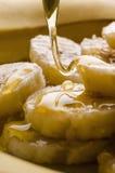 Hällande honung på skivor av bananen royaltyfri foto