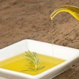 Hällande jungfrulig olivolja i en platta Arkivbilder