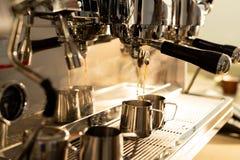 Hällande kaffe för espressomaskin in i tillbringaren royaltyfri fotografi