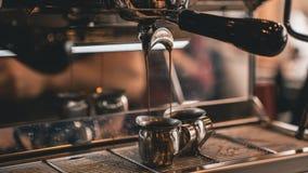 Hällande kaffe för espressotillverkare in i skott fotografering för bildbyråer