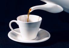Hällande kaffe från en kruka in i en kopp Arkivfoton