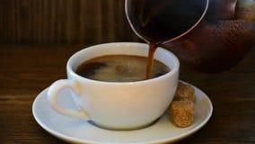 Hällande kaffe från kaffecezveturka in i koppen på trätabellen lager videofilmer
