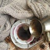 Hällande kaffe från kaffekrukan in i en porslinkopp Arkivfoto