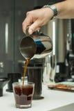Hällande kaffe in i ett exponeringsglas Royaltyfria Bilder