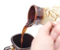 Hällande kaffe i kopp från cezve Royaltyfria Bilder