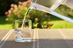 Hällande klart filtrerat vatten från en vattenfiltreringtillbringare in i ett exponeringsglas i grön sommarträdgård i en solig so royaltyfria foton