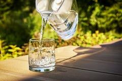 Hällande klart filtrerat vatten från en vattenfiltreringtillbringare in i ett exponeringsglas i grön sommarträdgård i en solig so royaltyfri fotografi